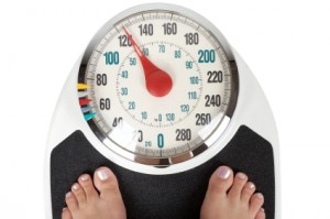 Woman on Weighing Scale Concerned with Weight Loss and Gain